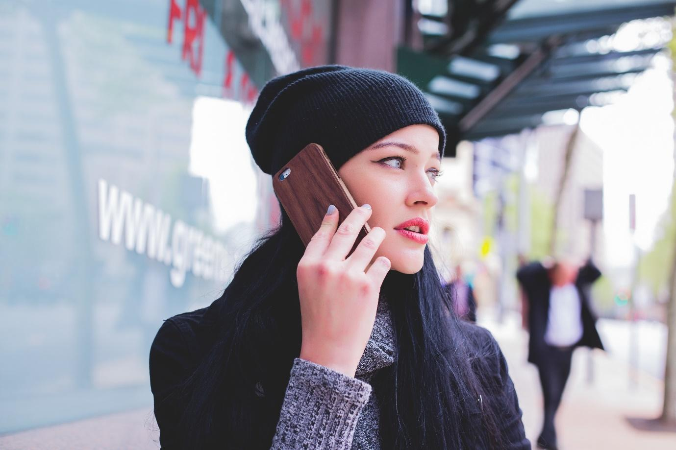 A person wearing a hat talking on a cell phone  Description automatically generated